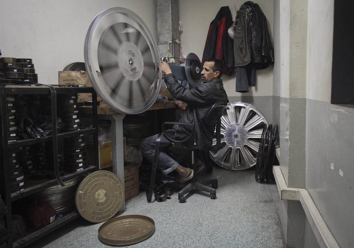 A projectionist rewinds a roll of film inside the projection room at Ariana Cinema in Kabul.