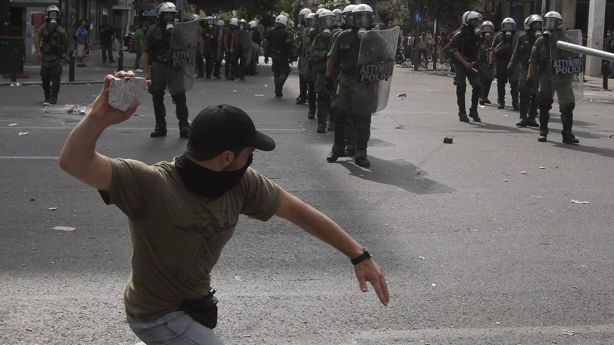 A protester throws a stone at policemen during riots in Athens this month.