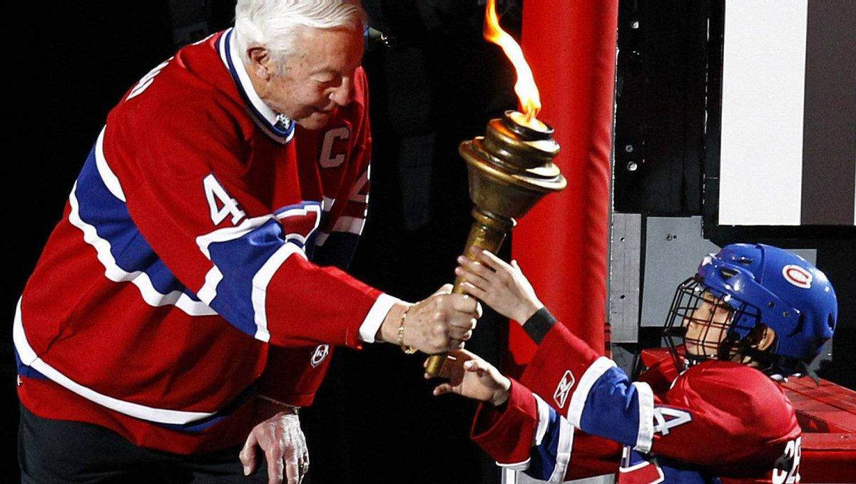 Montreal Canadiens great Jean Beliveau hands off a torch to a young hockey player before the Canadiens play the Boston Bruins in Game 3 of their NHL Eastern Conference quarter-final hockey game in Montreal April 18, 2011. REUTERS/Shaun Best