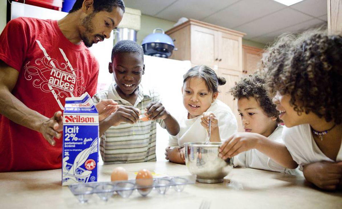Rian Scott, a Frontlines youth worker, helps the centre's children make breakfast.