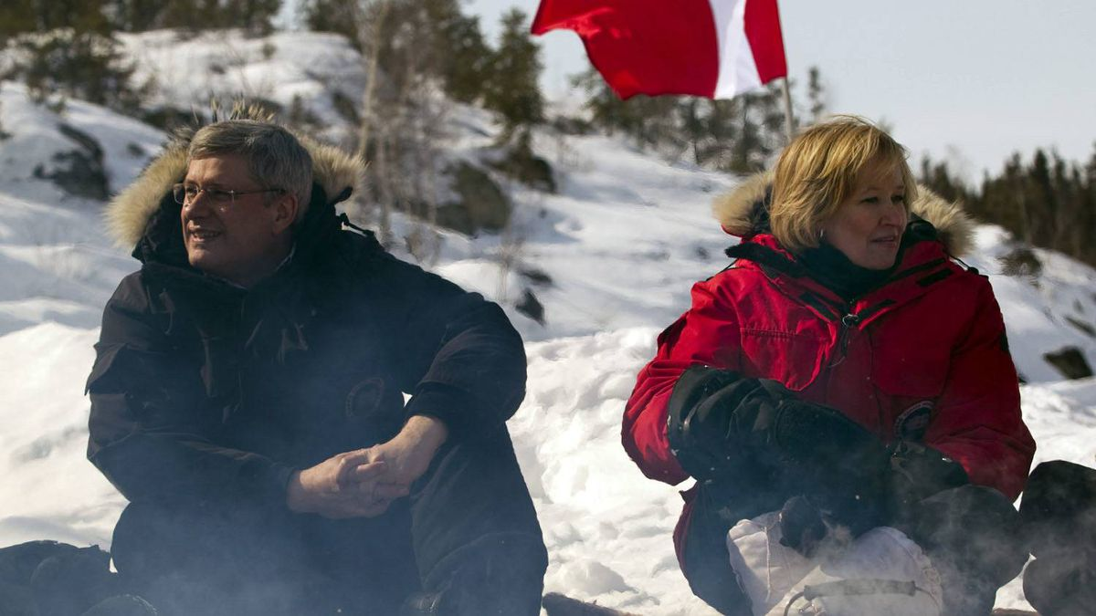 Conservative Leader Stephen Harper and his wife Laureen sit to sample Arctic char and bison cooked on a campfire during a campaign stop in Yellowknife.