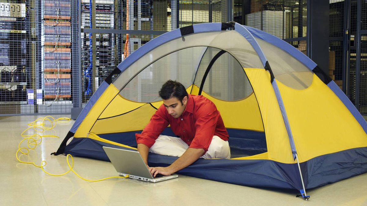 Man in tent using laptop in server room