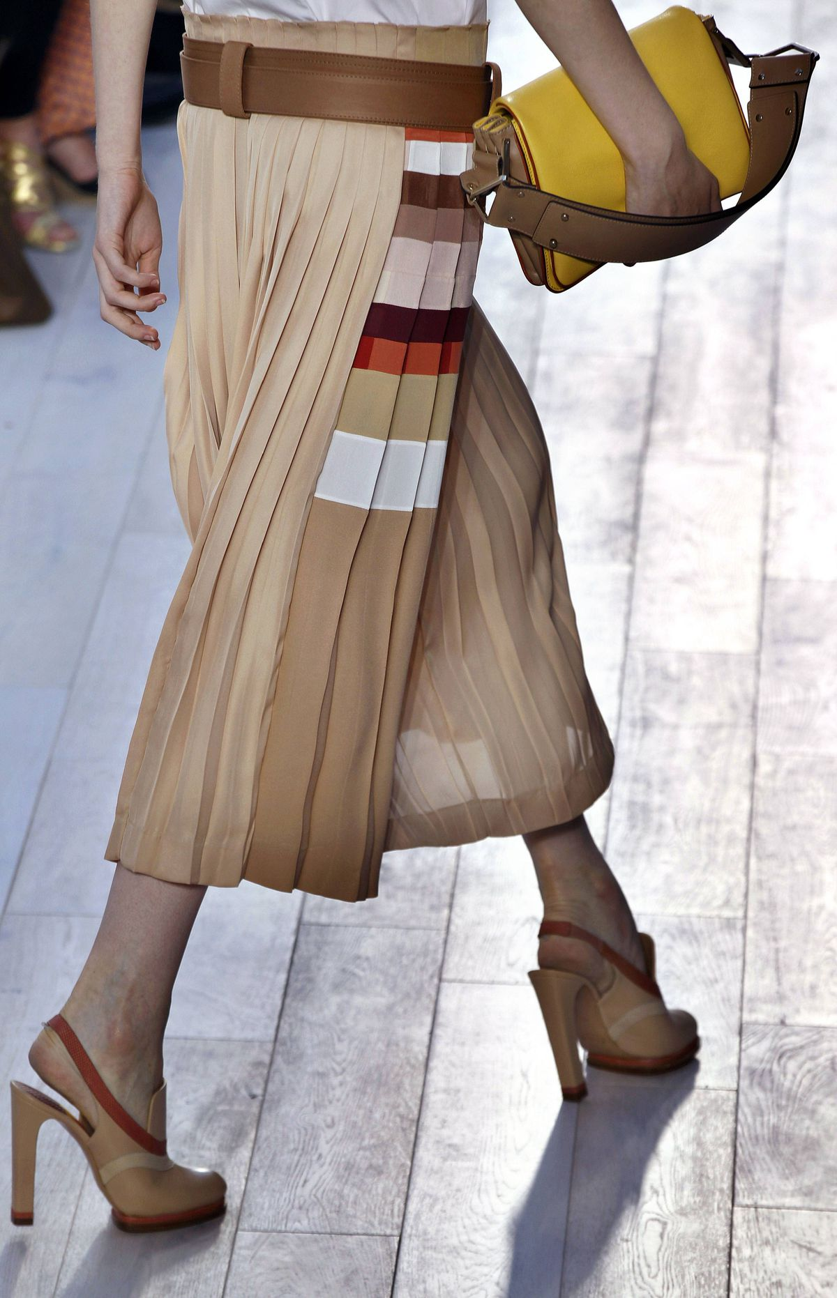 This is the first collection under the design direction of Clare Waight Keller (adieu, Hannah MacGibbon) so she's naturally feeling the need to prove herself, or at least impart a defined aesthetic. While the geometric skirt suggests distinctive graphic detail, the sling back comes across as awkward.