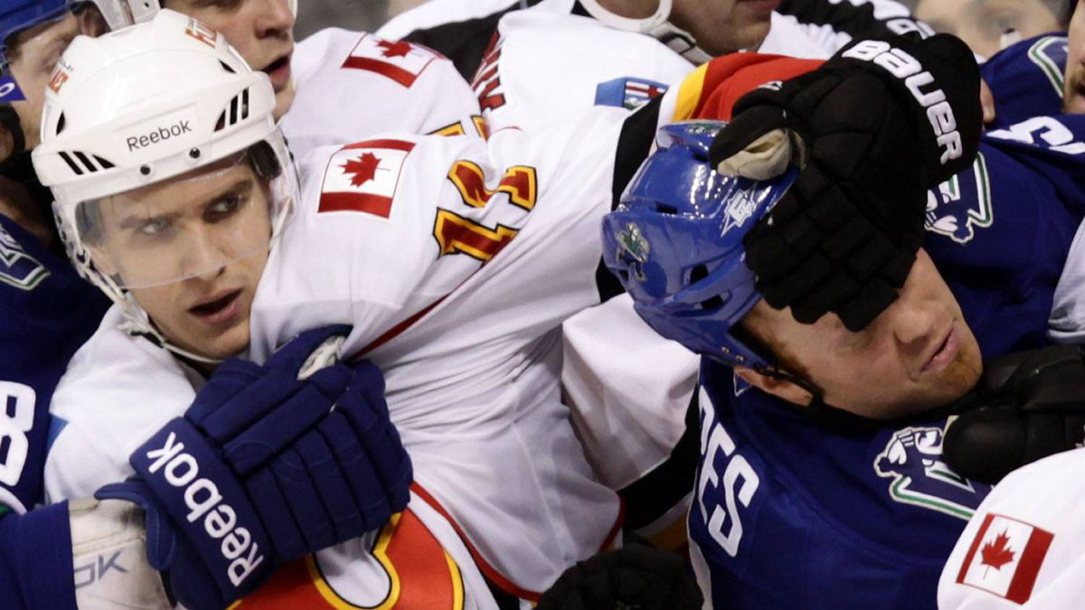 Calgary Flames' Mikael Backlund, left, of Sweden, grabs Vancouver Canucks' Raffi Torres by the head during the second period of an NHL hockey game in Vancouver, B.C., on Saturday February 12, 2011. The Canucks won 4-2. THE CANADIAN PRESS/Darryl Dyck