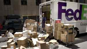 A FedEx worker looks over his packages on a New York street on Tuesday, May 29, 2007.