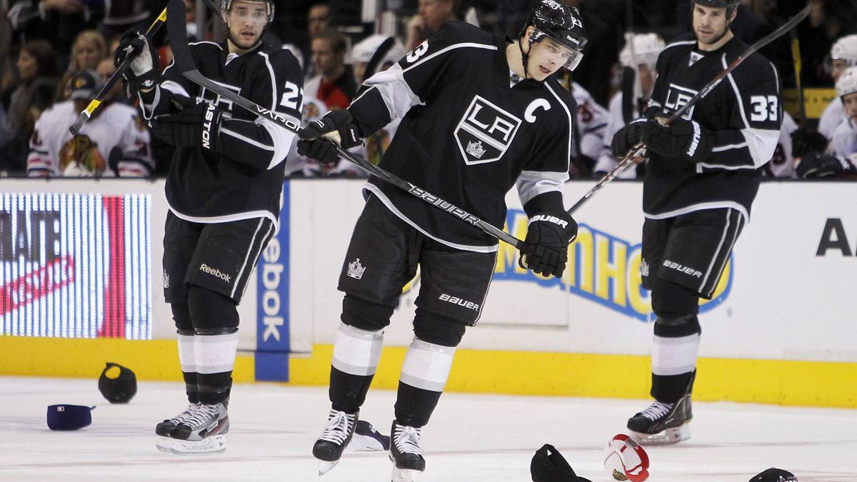 Los Angeles Kings right wing Dustin Brown, center, skates with defenseman Alec Martinez, left, and Willie Mitchell (33) around hats thrown by fans after scoring his third goal during the second period against the Chicago Blackhawks in an NHL hockey game in Los Angeles, Saturday, Feb. 25, 2012. The Kings won 4-0. (AP Photo/Alex Gallardo)