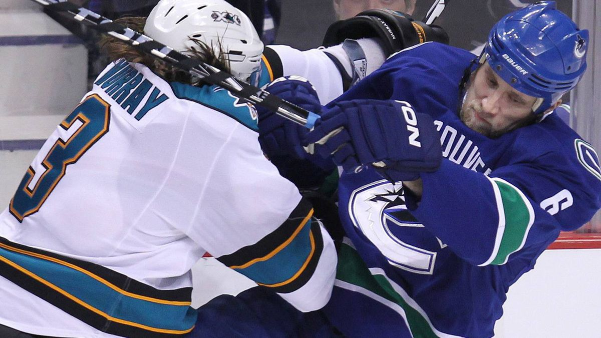 San Jose Sharks' Douglas Murray, of Sweden, left, hits Vancouver Canucks' Sami Salo, of Finland. THE CANADIAN PRESS/Jonathan Hayward