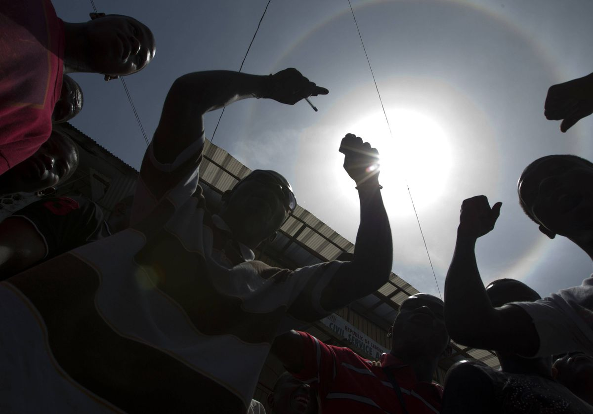 A group in downtown Monrovia, Liberia have a heated discussion on the streets after the Charles Taylor verdict was finally announced the sun was surrounded by a rainbow at the time- which people took to mean a variety of things.