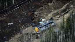 Workers collect oil in bins during the cleanup of the Rainbow pipeline break northeast of Peace River, Alta.
