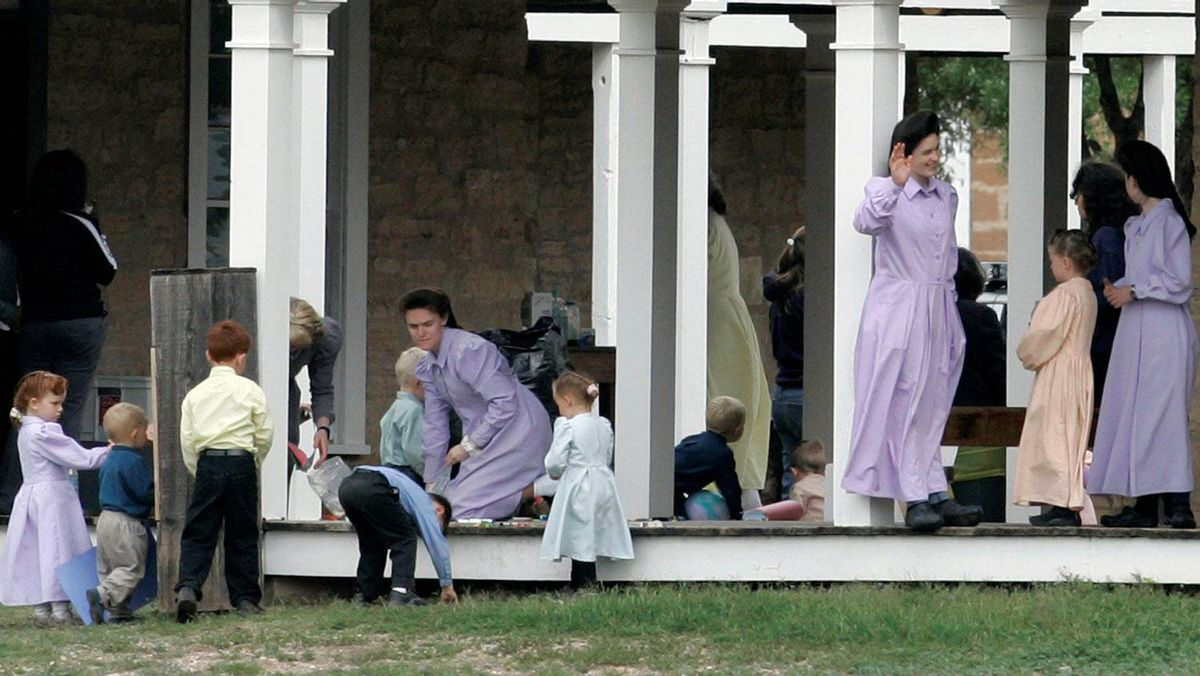 Adults and children, members of the Fundamentalist Church of Jesus Christ of Latter Day Saints, gather beneath a covered porch at one of the structures at their temporary housing, Fort Concho National Historic Landmark, in San Angelo, Texas, Wednesday, April 9, 2008.