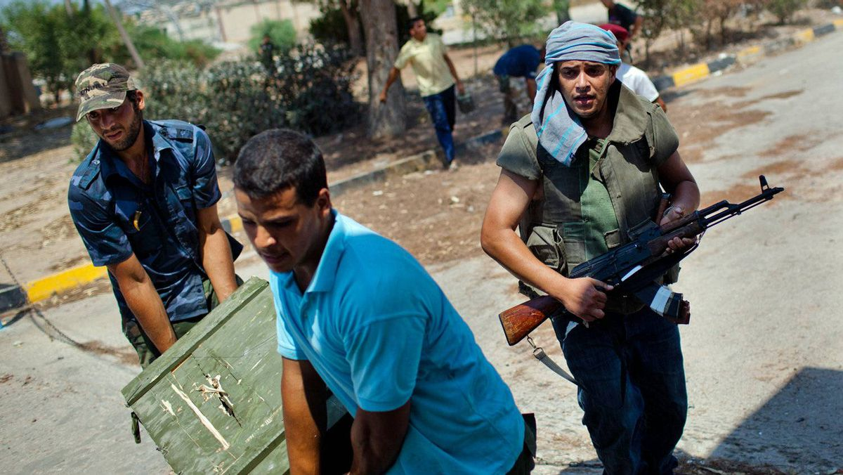 Libyan rebel soldiers loot weapons from an ex-Gaddafi military compound as they advance in Tripoli on Aug. 26, 2011.