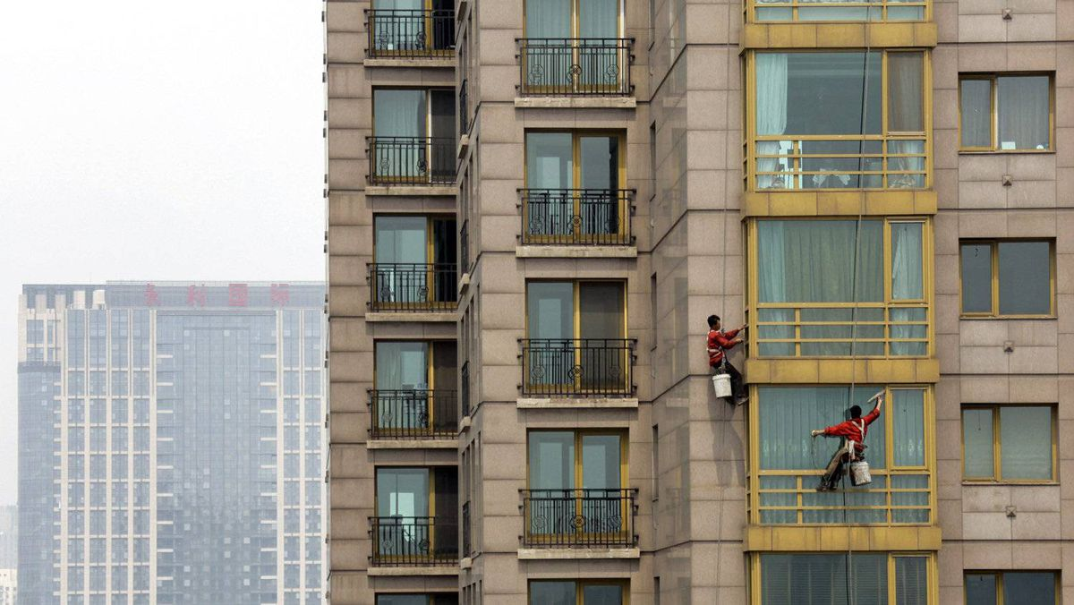 Workers clean the windows of an apartment block at a residential area in Beijing May 9 2012.