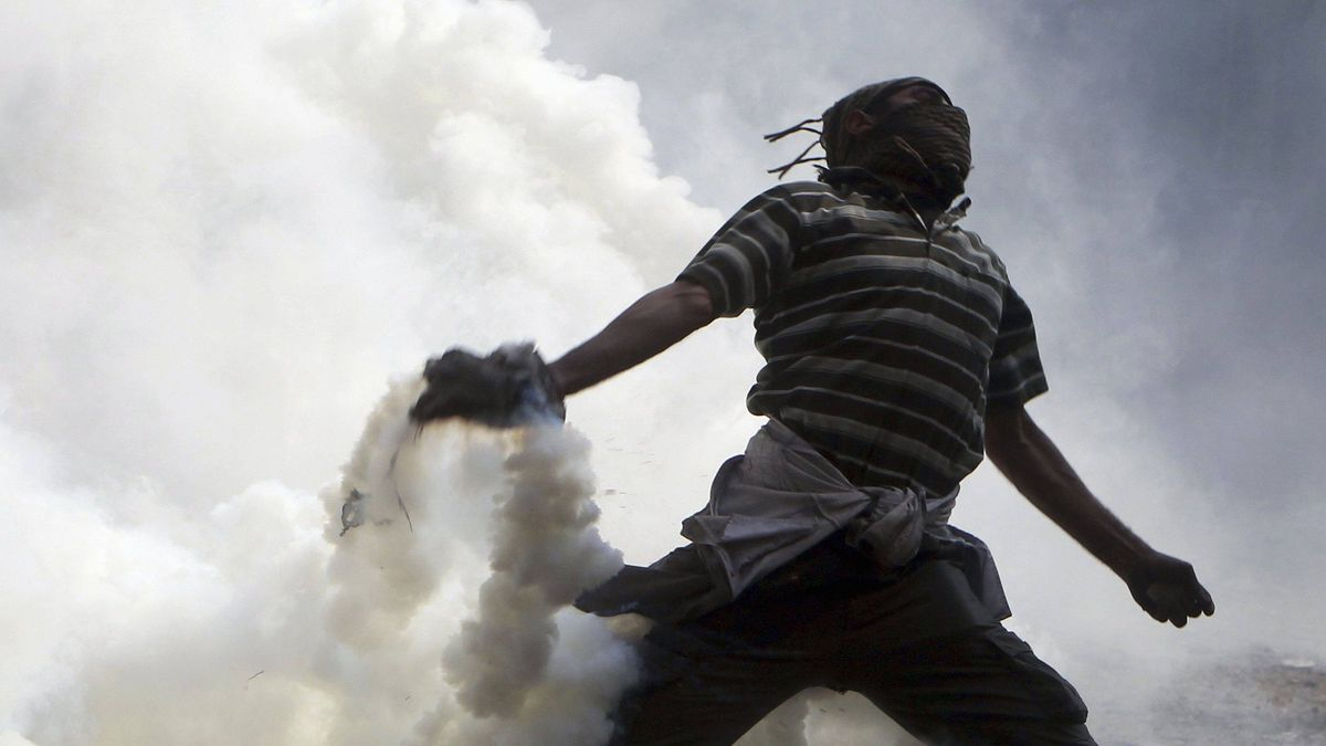 A protester throws back a tear gas canister at police during clashes along a road which leads to the Interior Ministry, near Tahrir Square in Cairo Nov. 22, 2011.