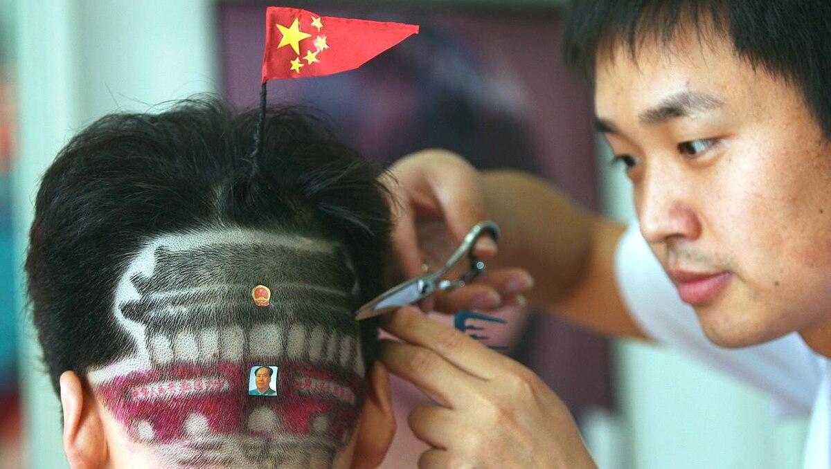 A man gets haircut featuring Tiananmen Gate at a barber shop in Zhengzhou