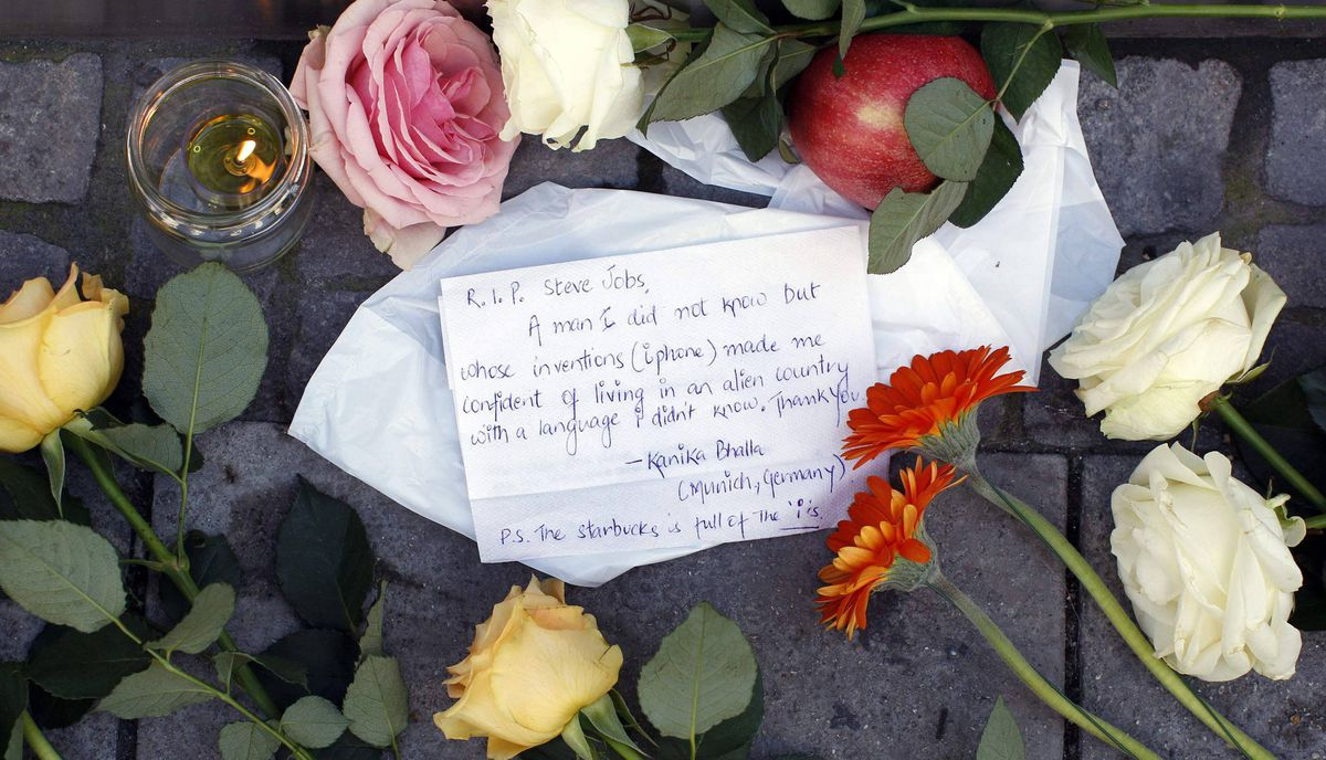 A tribute, flowers, candles and an apple are placed in front of an Apple store in Munich, Germany October 6, 2011.