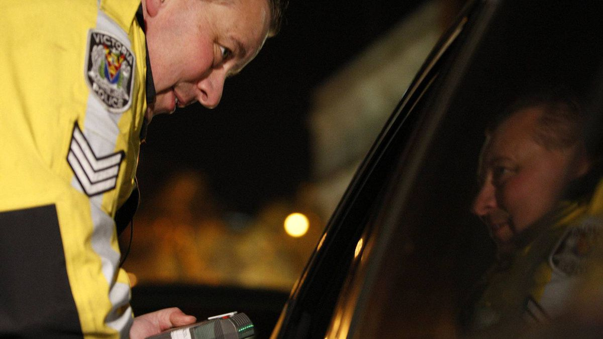A Victoria Police officer prepares to administer an Approved Screening Device(breathalyzer) to the driver of a vehicle during a check stop on Yates St. in downtown Victoria.
