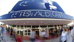 People walk past the Festival Palace in Cannes on May 15, 2012. The Cannes Film Festival runs from May 16 to 27.