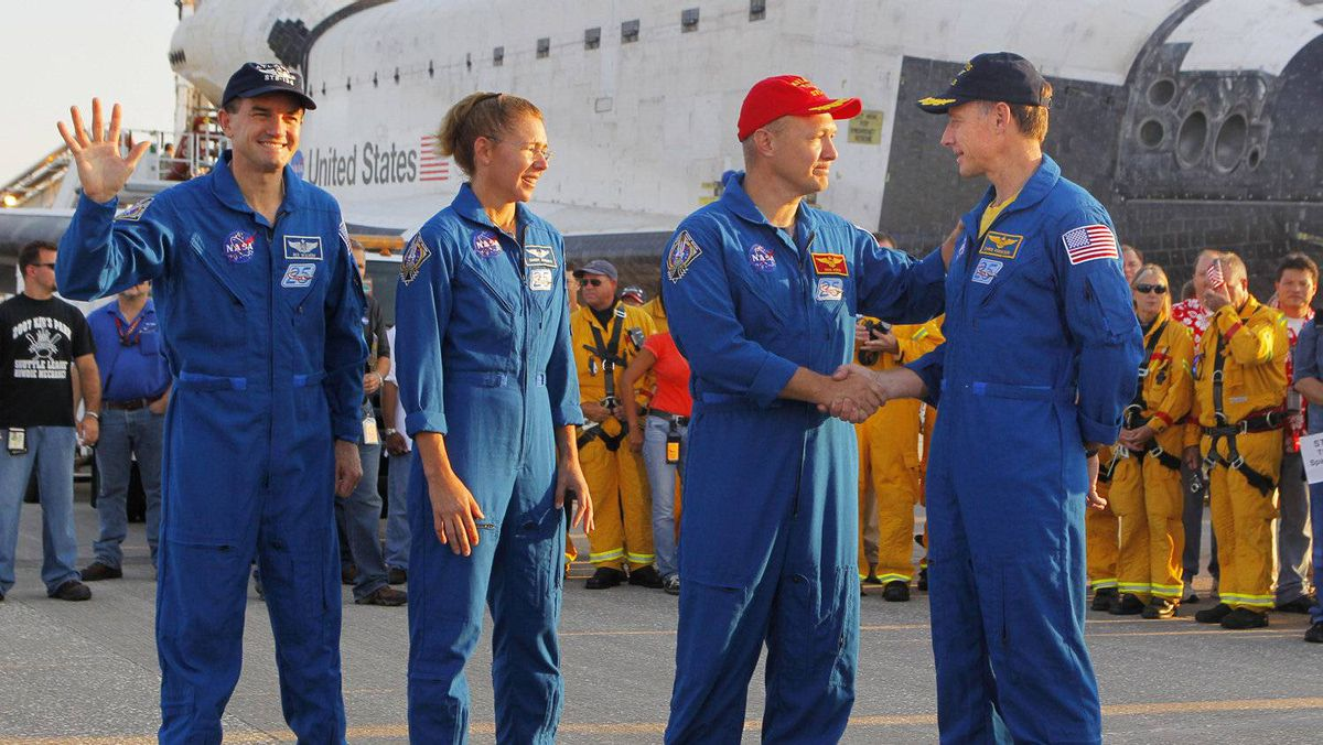 Space shuttle Atlantis pilot Doug Hurley (2nd R) shakes hands with commander Chris Ferguson (R) as mission specialists Sandy Magnus (2nd L) and Rex Walheim (L) watch on the runway July 21, 2011 at Kennedy Space Center in Florida.