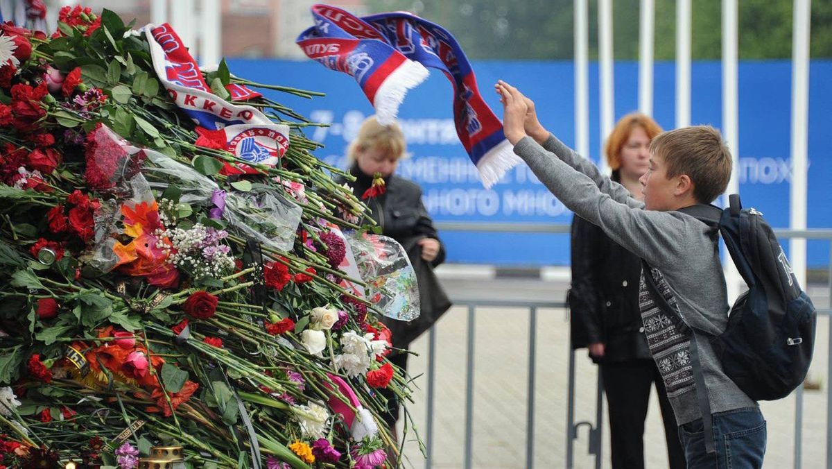 A boy throws a scarf of his team colours onto the flowers placed in front of the Arena-2000 stadium, the home venue of Russian ice hockey team Lokomotiv Yaroslavl in the city of Yaroslavl.