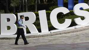 A traffic policeman walks past a signage decoration for BRICS Summit outside the Sheraton Hotel, the venue of BRICS (Brazil, Russia, India, China and South Africa) Summit in Sanya, China's Hainan province, April 13, 2011.