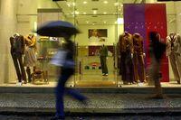 Pedestrians walk past a shop on a rainy day in Rio de Janeiro, Brazil, Thursday, July, 2001.
