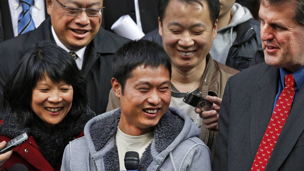 Flanked by NDP MP Olivia Chow, Toronto shopkeeper David Chen leaves court on Oct 29, 2010, after charges in his case were dropped.