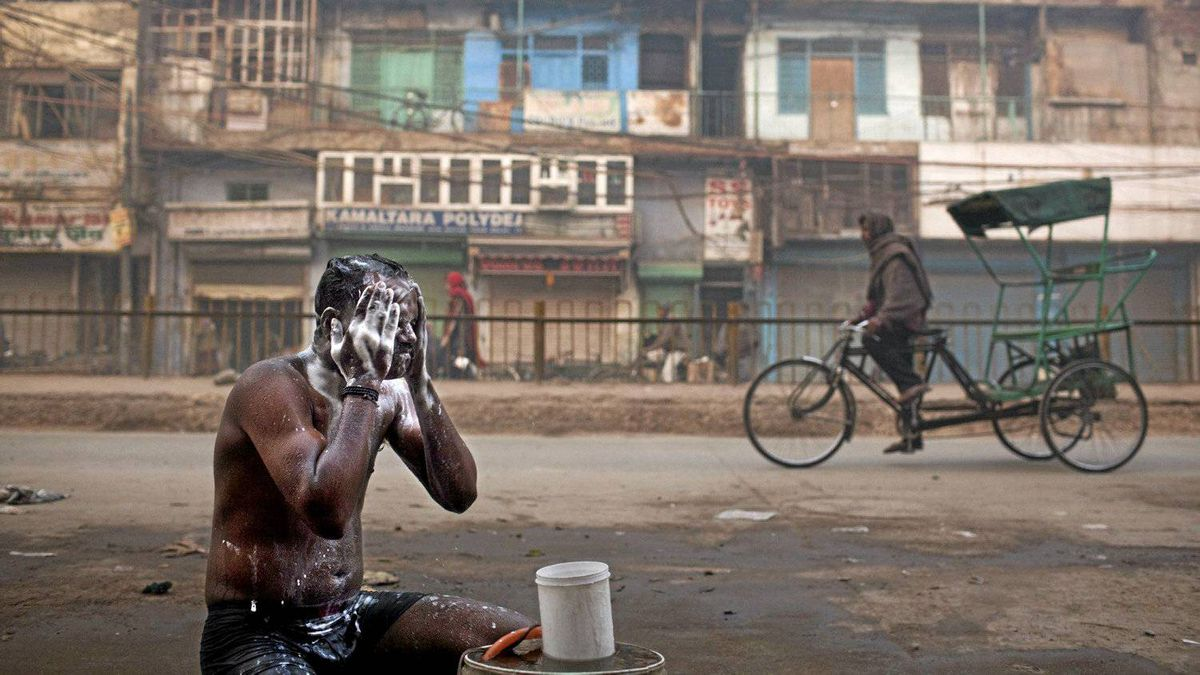 An Indian man bathes on a street as a rickshaw driver pedals past on a cold morning in New Delhi, Dec. 28, 2011. Economic growth in the world's most-populous nation is expected to drop below 6 per cent.