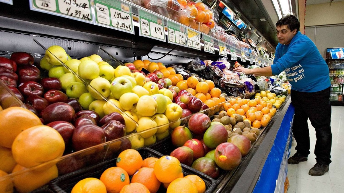 Grocery store owner Gilles Robin works on his fruits vegetable display on Nov. 28 2006 in the Breakeyville, Que.
