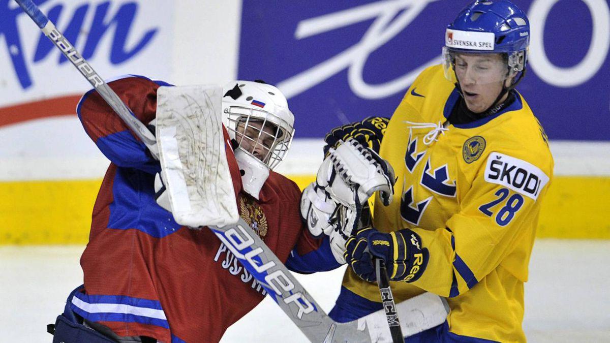 Russia goaltender Andrei Makarov and Sweden's Erik Thorell cross sticks.