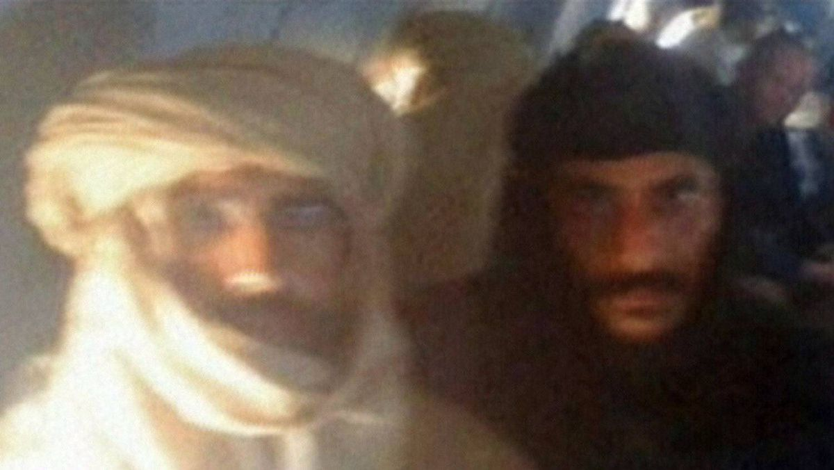 An image grab taken from the Libya Al-Ahrar TV station on November 19, 2011 shows Seif al-Islam (L), the fugitive son of ousted and killed Libyan leader Moamer Kadhafi, guarded by a Libyan fighter as they sit on an aircraft at an air strip in the town of Zintan, after he was captured in southern Libya.