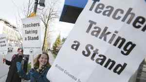 Teachers from General Brock Elementary School wave to cars outside the school and hold up signs while on strike in Vancouver, British Columbia March 5, 2012.