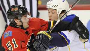 Calgary Flames' Roman Horak (L) tries to get past St. Louis Blues' Kent Huskins during the first period of their NHL hockey game in Calgary, Alberta, October 28, 2011. REUTERS/Todd Korol