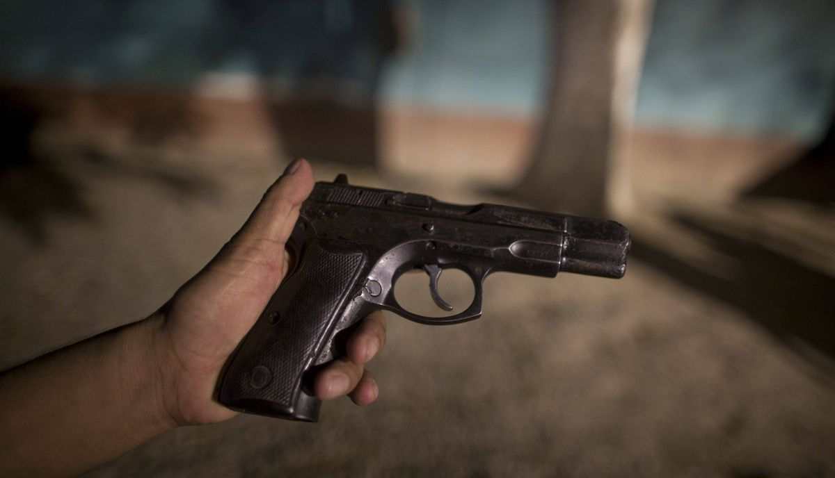 A police officer shows his damaged weapon in the police station in San Pedro Sula, Honduras, MArch 8, 2012.