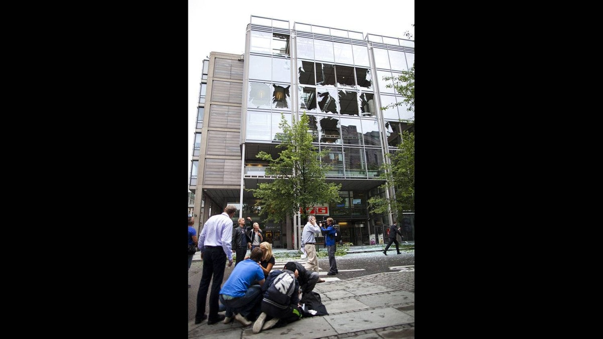 People are treated at the scene after an explosion near the government buildings in Norway's capital Oslo on July 22, 2011. At least one person was killed by the powerful explosion which ripped through government and media buildings.