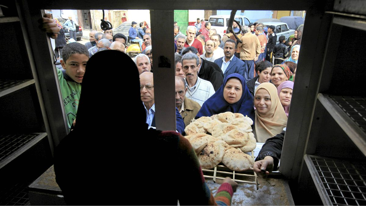 Egyptians crowed to buy bread before the start of the evening curfew in Cairo, Egypt, Monday, Jan. 31, 2011.