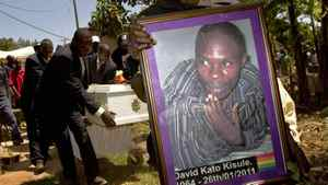 A members of the Ugandan gay community carries a picture of murdered gay activist David Kato during his funeral near Mataba, on January 28, 2011.