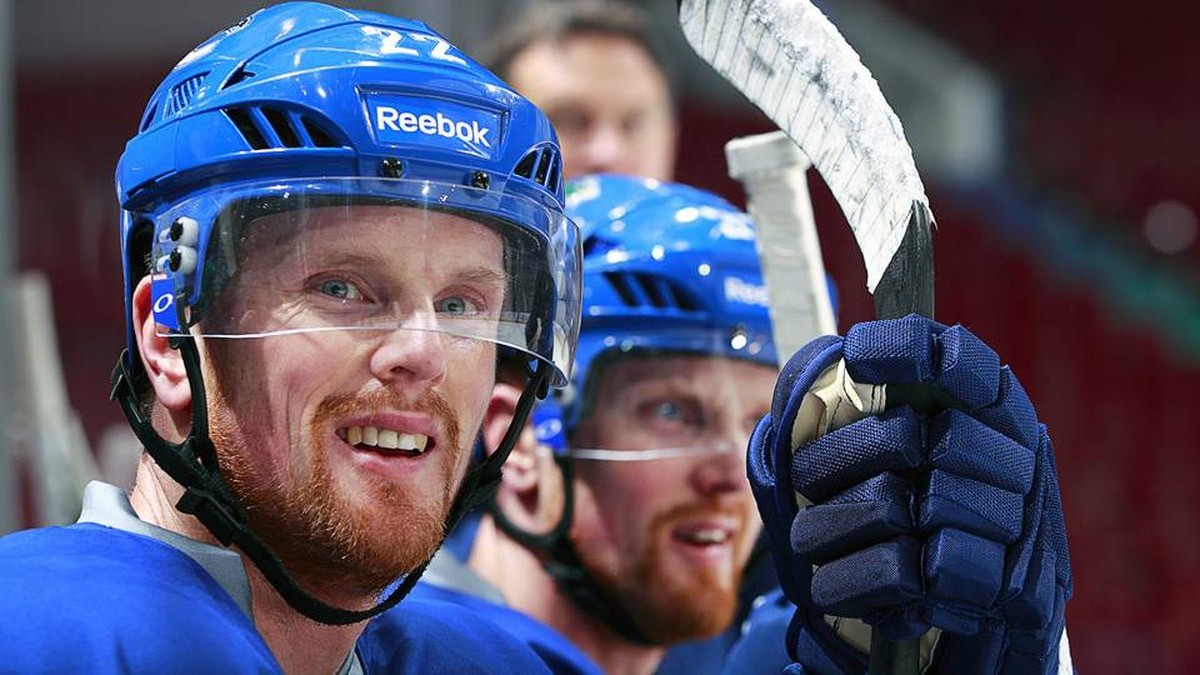 Daniel Sedin (left) of the Vancouver Canucks and teammate and twin brother Henrik Sedin look on from the bench during their first postseason practice at Rogers Arena in Vancouver, Canada April 9, 2012.
