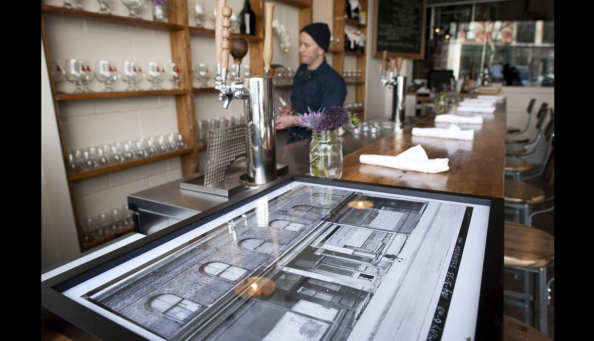 A historic photograph of Ossington Ave. from 1943 rests on the bar as Bellwoods Brewery co-owner Mike Clark gets ready to open the micro brewery in Toronto, Ont. Thursday, April 12/2012. (Photo by Kevin Van Paassen/The Globe and Mail)