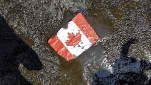 A placard with the Canadian flag rests on the ground covered in oil as demonstrators conduct a die-in to protest against the Keystone Pipeline and the Alberta Tar Sands outside of the Canadian Consulate in downtown Chicago, Thursday, May 17, 2012.