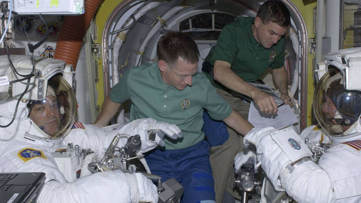 Spacewalkers Mike Fossum (R) and Ron Garan (L) are assisted by space shuttle Atlantis Commander Chris Ferguson (2nd L) and Rex Walheim in the International Space Station's Quest airlock prior to their July 12 spacewalk in this photo provided by NASA.