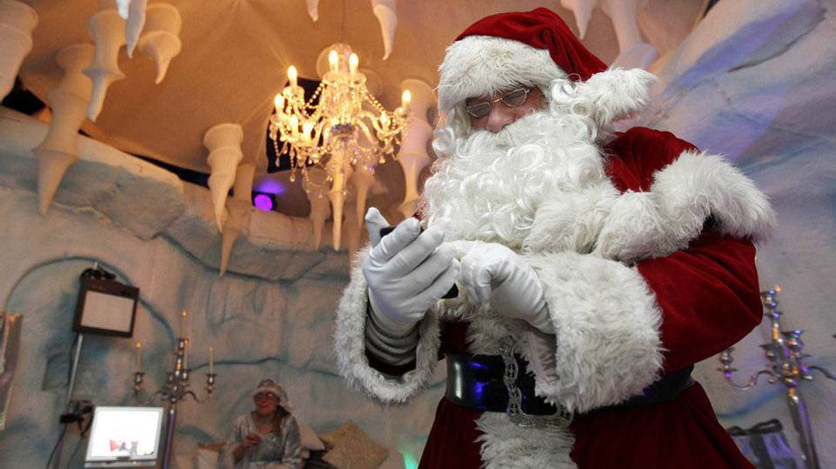Santa checks his mobile phone during at break at Santa's Grotto in Selfridges department store in London.