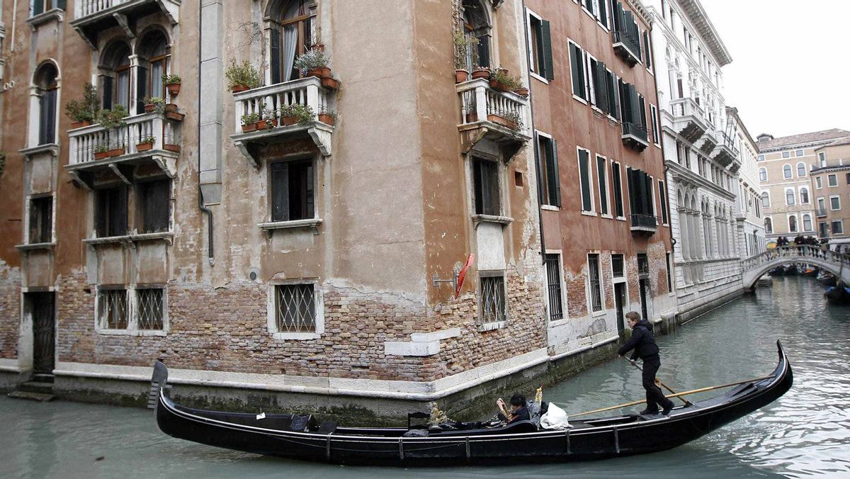 A gondolier rows his gondola in a canal in Venice.