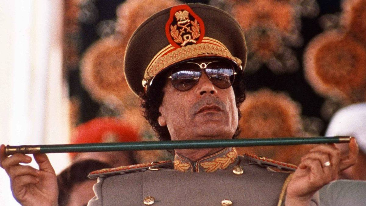 In this Sept. 1, 1987 file photo, Libyan leader Col. Moammar Gadhafi, holds a baton as he sits to review Libyan troops during the 18th anniversary celebration of Libya's revolution in Tripoli.