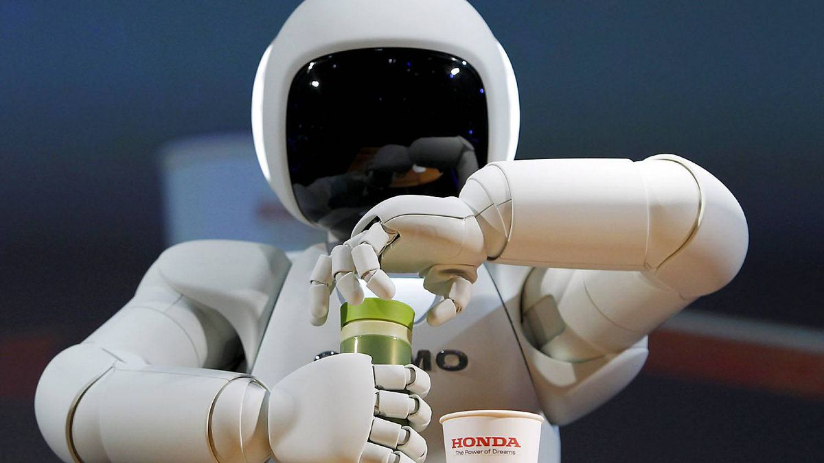 Honda Motor Co.'s Asimo humanoid robot opens the top of a bottle to pour a drink into a cup during a news conference at the 42nd Tokyo Motor Show in Tokyo November 30, 2011.