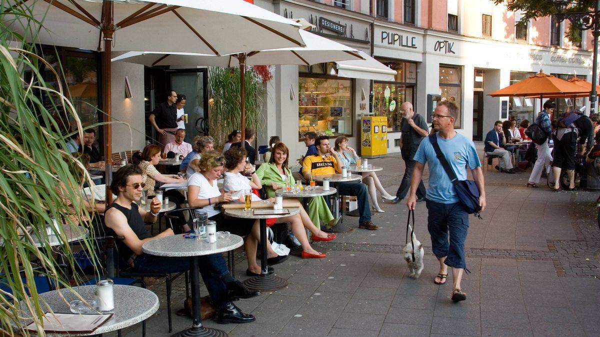 AMWX5B Germany Munich people sitting outside Interview cafe located at Gartnerplatz around the trendy Glockenbachviertel neighbourhood
