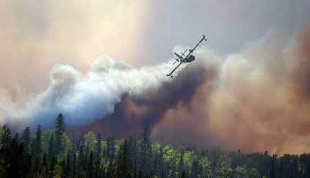 A water bomber helps crews from Kirkland Lake, Ont., and the province's Natural Resources ministry fight a nearby forest fire on May 21, 2012.