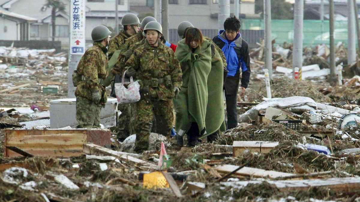 Members of the Japan Self-Defence Forces assist evacuees as they walk through a street clogged with debris in Sendai city, Miyagi prefecture on March 12, 2011.