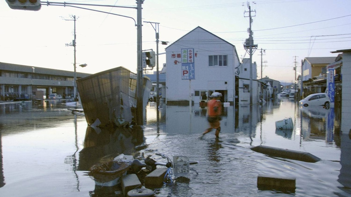 A man wades through a flooded street after tsunami spawned by a powerful earthquake in Iwaki, Fukushima prefecture.