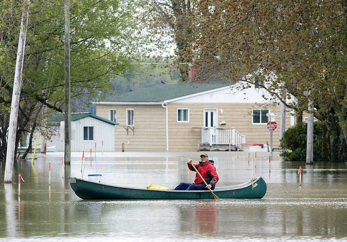 A man paddles a canoe through a flooded street in the town of St-Blaise, Que. Quebecers living along the swollen Richelieu River are facing the grim prospect of leaving their flooded homes - again.
