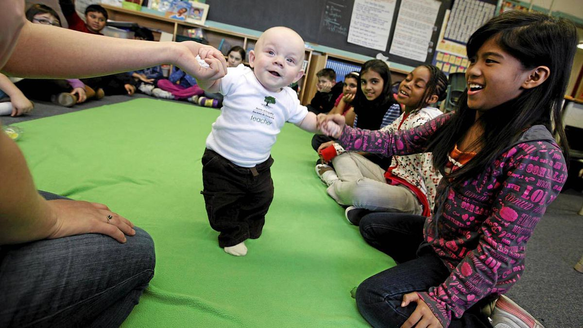 Nine-year-old Joyce Garsain helps eight-month-old Patrick Duffy as a grade four class looks on at George Webster Elementary school in Toronto. Roots of Empathy is an evidence-based classroom program that has shown dramatic effect in reducing levels of aggression among schoolchildren. Deborah Baic/The Globe and Mail